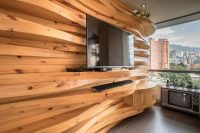 A Wavy Wood Accent Wall Creates Multiple Shelves In This