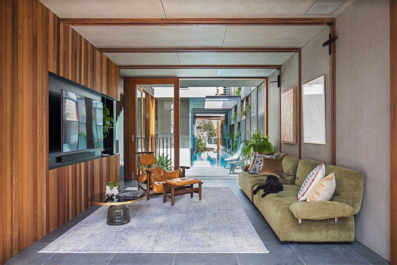 This contemporary media room has a wood accent wall and sliding glass doors that open up to the pool deck and the above ground swimming pool.
