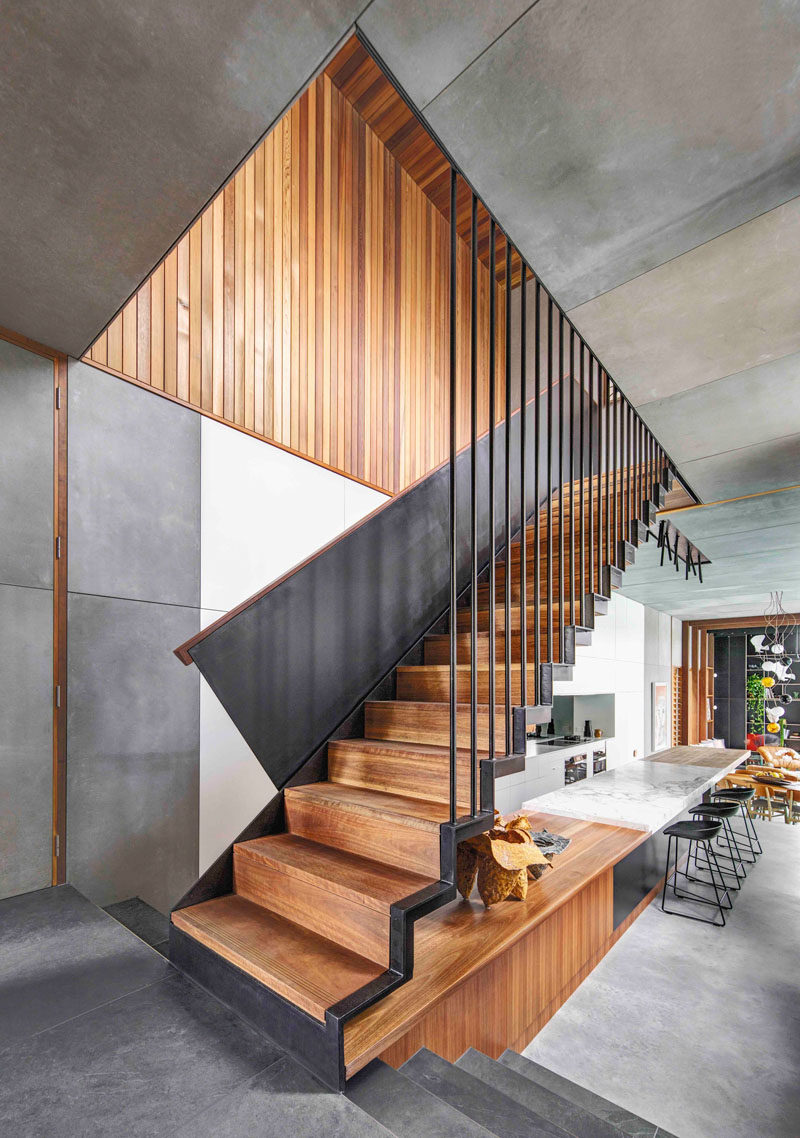 The steel and wood stairs in this modern house lead to the upper floor of the home that houses the bedrooms.