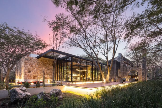 This modern restaurant in Mexico, with plenty of glass and wood, has been built inside a 19th century engine house of a farm that was in disrepair.