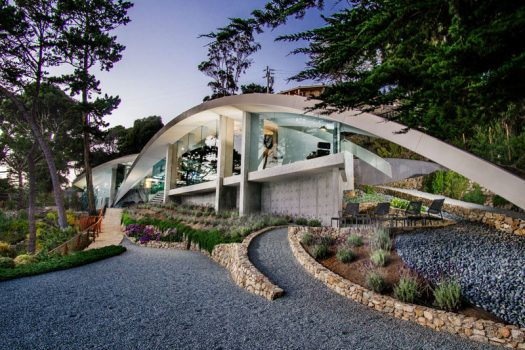 This modern house, designed by architect Wallace Cunningham, overlooks the ocean in Carmel, California, and has a sculptural appearance with glass walls and a curved stainless steel roof.