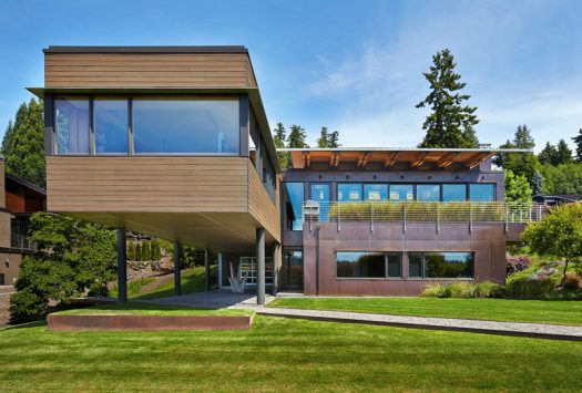 Dark-stained cedar siding and copper panels cover this modern house that has a cantilever and is nestled into a hillside on Mercer Island in Washington. #CedarSiding #CopperPanels #ModernHouse
