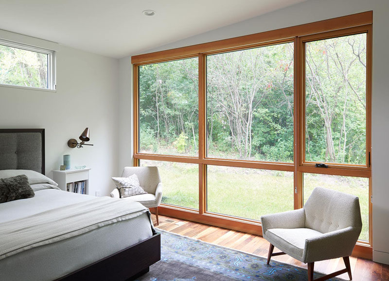 This modern bedroom has large windows that become the focal point in the room as the wood frames of the windows break up the mostly white room. #Windows #Bedroom