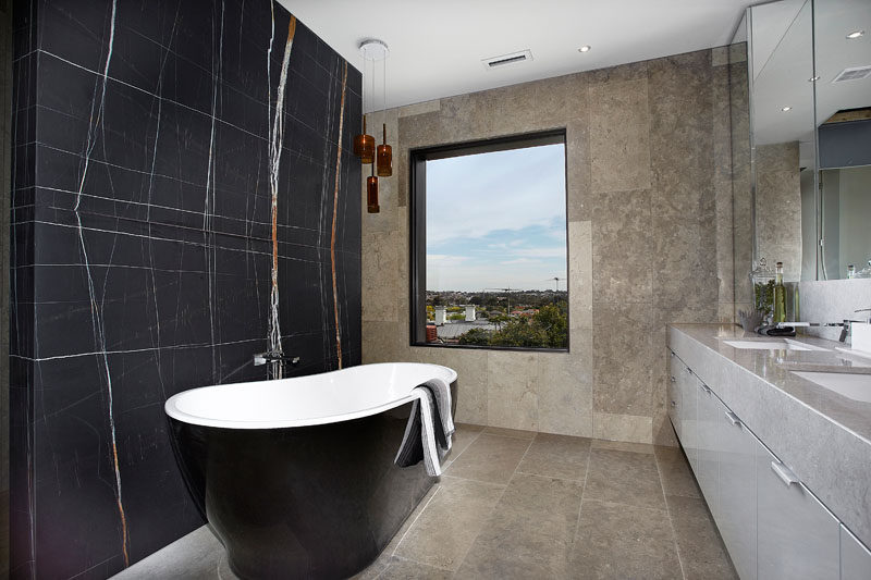 In the masterensuite bathroom there's a freestanding bath tub and double bowl vanity unit. Floor to ceiling marble and stone completes the theme of a luxury hotel retreat. #ModernBathroom