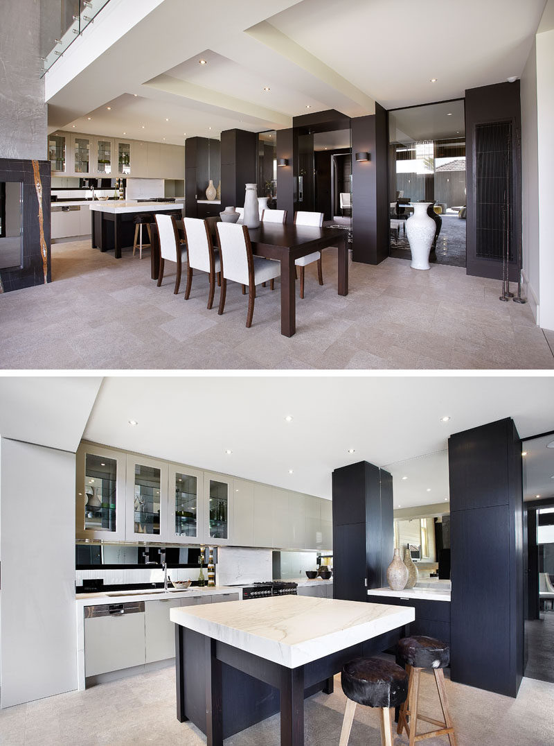 This contemporary dining room has a dark wood dining table, while in the kitchen, light colored cabinets contrast the darker cabinets and help to keep the space bright. #DiningRoom #Kitchen