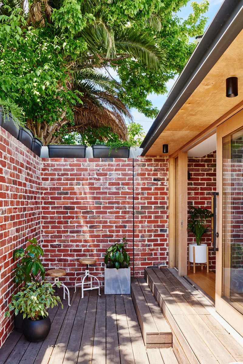 Red brick paving from the backyard has been recycled and now used as an internal feature wall and an external brick wall. #BrickAccentWall #BrickWall #OutdoorSpace