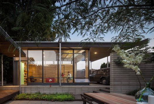 This modern backyard studio has floor-to-ceiling glass walls and a carport. #ModernBackyardStudio #Architecture