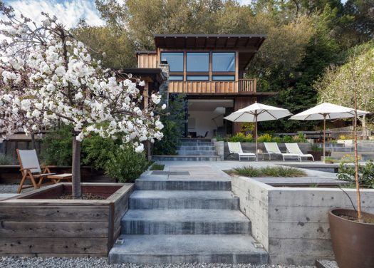 A two-storey addition with board and batten wood siding was added to a small cottage in California. #ModernAddition #Architecture #Cottage #Landscaping