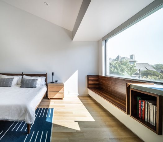 As part of a modern residential interior renovation, architect and interior design firm OFFICIAL, included a wood-lined built-in window seat and bookshelf in the master bedroom. #WindowSeat #Bookshelf #MasterBedroom