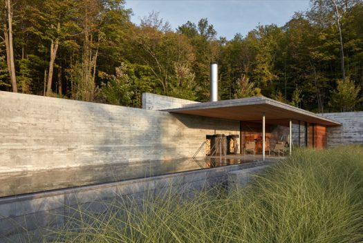 This modern concrete, wood, and glass pool house sits next to an infinity lap pool and hot tub, and features an outdoor fireplace, a gym, lounge, and changing areas. #PoolHouse #SwimmingPool #Architecture
