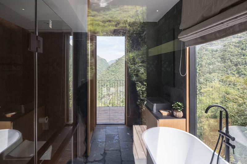 In this holiday cabin, the modern bathroom has a dark interior with a white freestanding bathtub positioned next to the window. #BathroomDesign #DarkBathroom #ModernBathroom