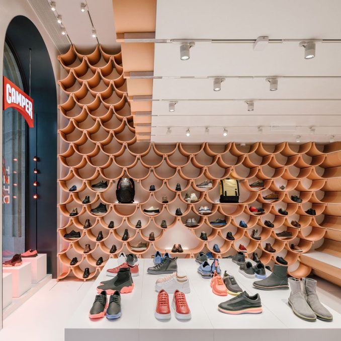 Inside, the pattern on the walls is revealed to be made up of roof-tile like ceramic elements, that neatly complement each other. #RetailStoreDesign #InteriorDesign #RetailDesign