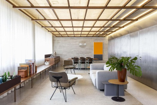 Throughout the main living space of this modern apartment, is a wood grid that has been suspended from the ceiling, that not only brings warmth to the interior, but also provides indirect lighting. #WoodGridCeiling #ModernApartment #HiddenLighting