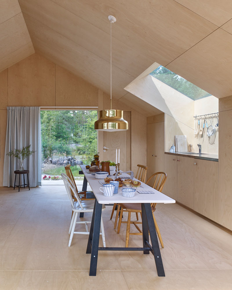 Windows filter the light through to the bright interior of this modern house that features birch plywood walls, ceiling, and floor. #PlywoodWalls #PlywoodInterior #Windows #Kitchen #Dining