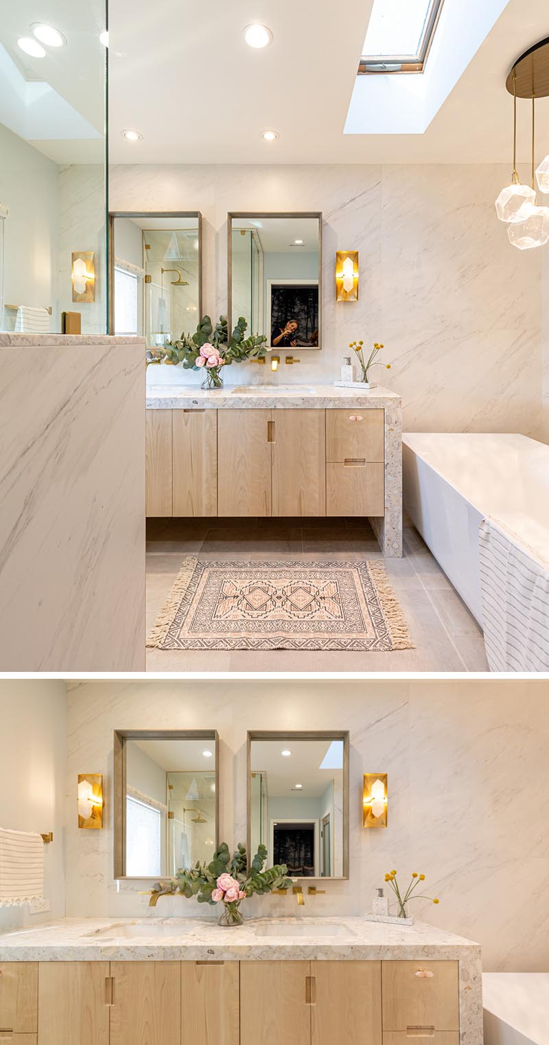 The soft color palette of this modern bathroom plays well with the floral and brass accents throughout. The wood vanity cabinets are hardware free, with just finger notches providing access to the storage within. #ModernBathroom #BathroomDesign #Skylight #Vanity