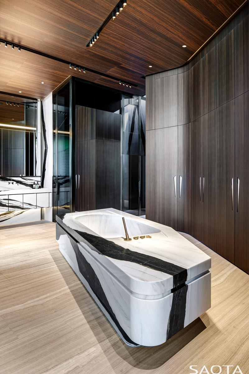 In this modern bathroom, tall wood closets line the wall, while a stone bathtub is centrally located. #ModernBathroom #BathroomDesign #StoneBathtub