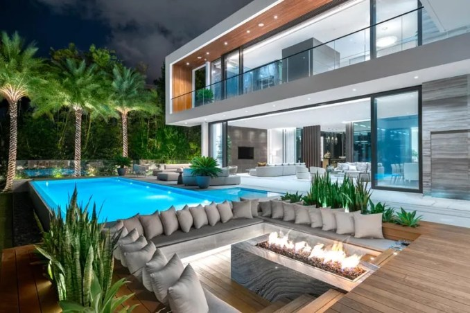 This outdoor sunken lounge has steps that lead down to wrap around bench seating with hidden lighting, and a firepit. #SunkenLounge #Landscaping #OutdoorSeating