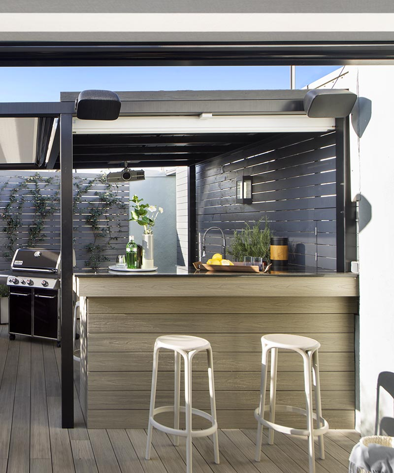 This modern outdoor terrace has a bar area with seating. A hidden detail is the white screen that can be pulled down to show a movie on. #Terrace #OutdoorBar #Projector