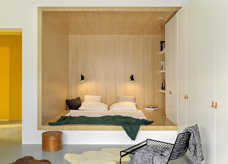 Instead of having a freestanding bed, the designers made use of an odd shaped corner small positioned the bed within the base of its own wood-lined niche, allowing for more floor space by the large windows. #BedroomIdea #BedNook #BedNiche #BuiltInBed #InteriorDesign #ModernBedroom