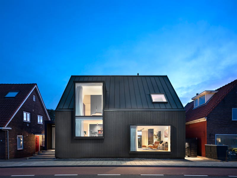 The exterior of this modern house features black wooden ventilated facade in combination with a black metal roof. #BlackHouse #ModernBlackHouse #Architecture