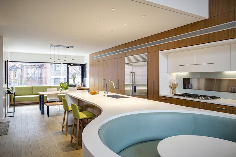 The custom-designed white Corian island countertop in this modern kitchen, has a rectangular shape at one end, before transitioning into a curved split design that wraps around the soft blue banquette seating that makes up the integrated breakfast nook. #KitchenDesign #ModernKitchen #BreakfastNook #BanquetteSeating #KitchenIsland