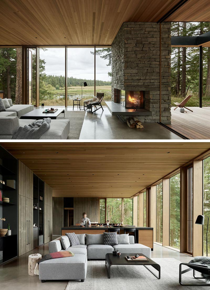 In this modern open plan living room, a stone fireplace with a concrete hearth, and the views of the land are the main focal points. #LivingRoom #Fireplace #Windows #WoodCeiling #ModernHouse