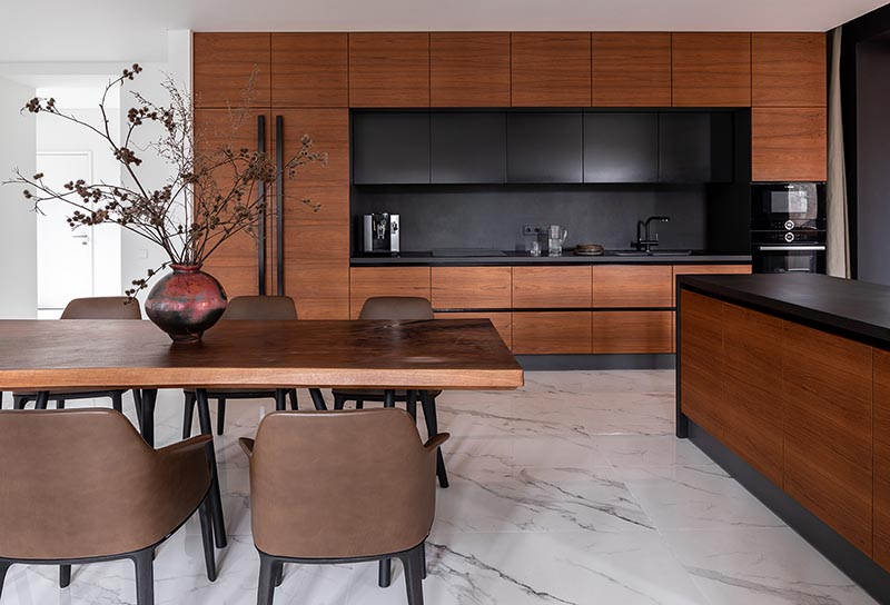 This modern warm wood kitchen and dining area includes a palette of shades ranging from cinnamon to chestnut, as well as darker elements, like the hardware and kitchen backsplash. #WarmWoodKitchen #WoodKitchen #KitchenDesign #WoodDiningTable