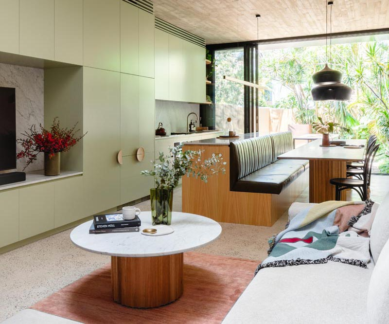 A modern light green kitchen with an island that transitions into a bench for dining table seating.
