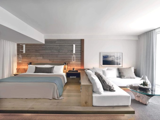 A hotel room with a wood platform, salvaged driftwood walls, and a built-in wrap-around daybed couch.