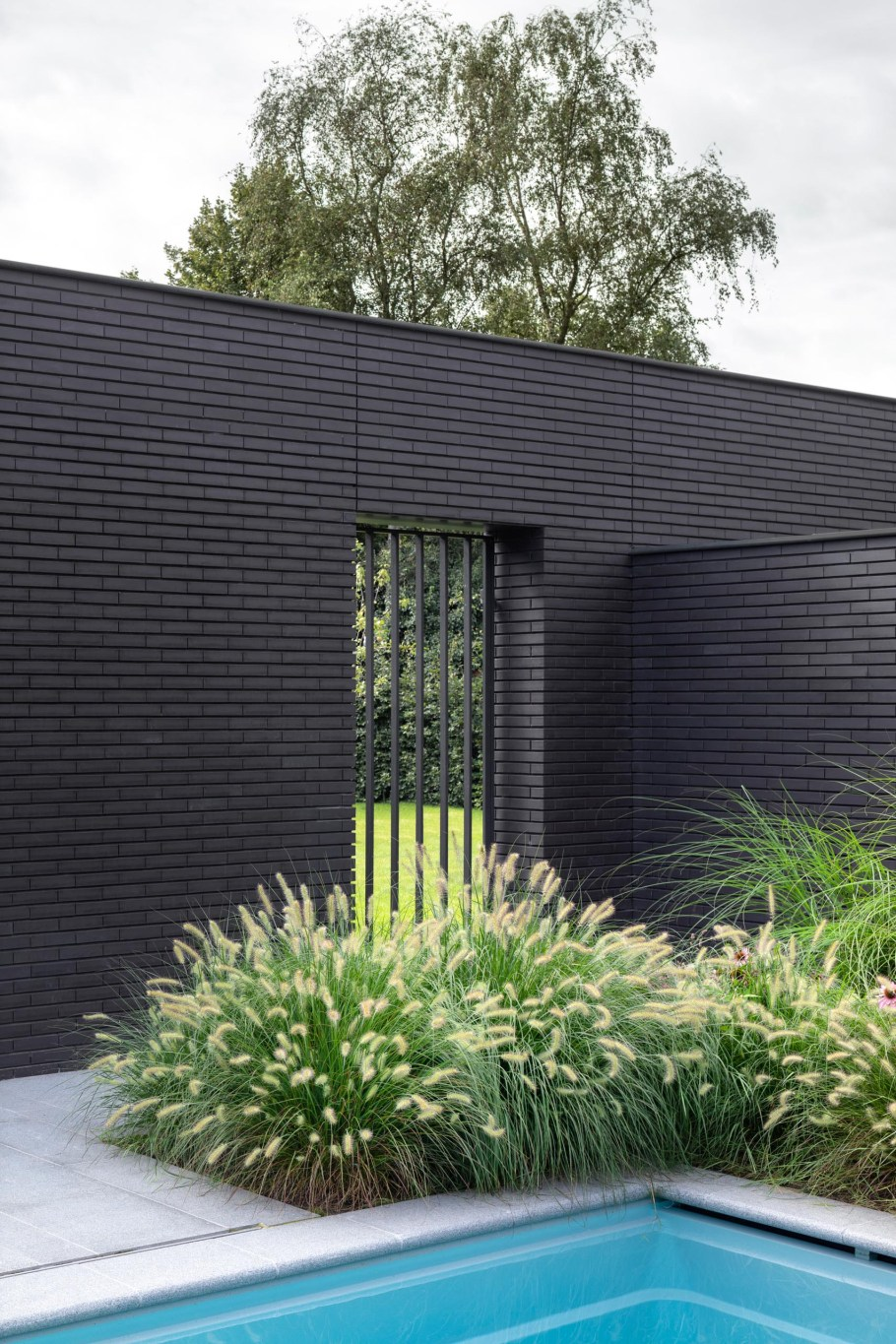 A black brick home exterior with lush gardens and a swimming pool.
