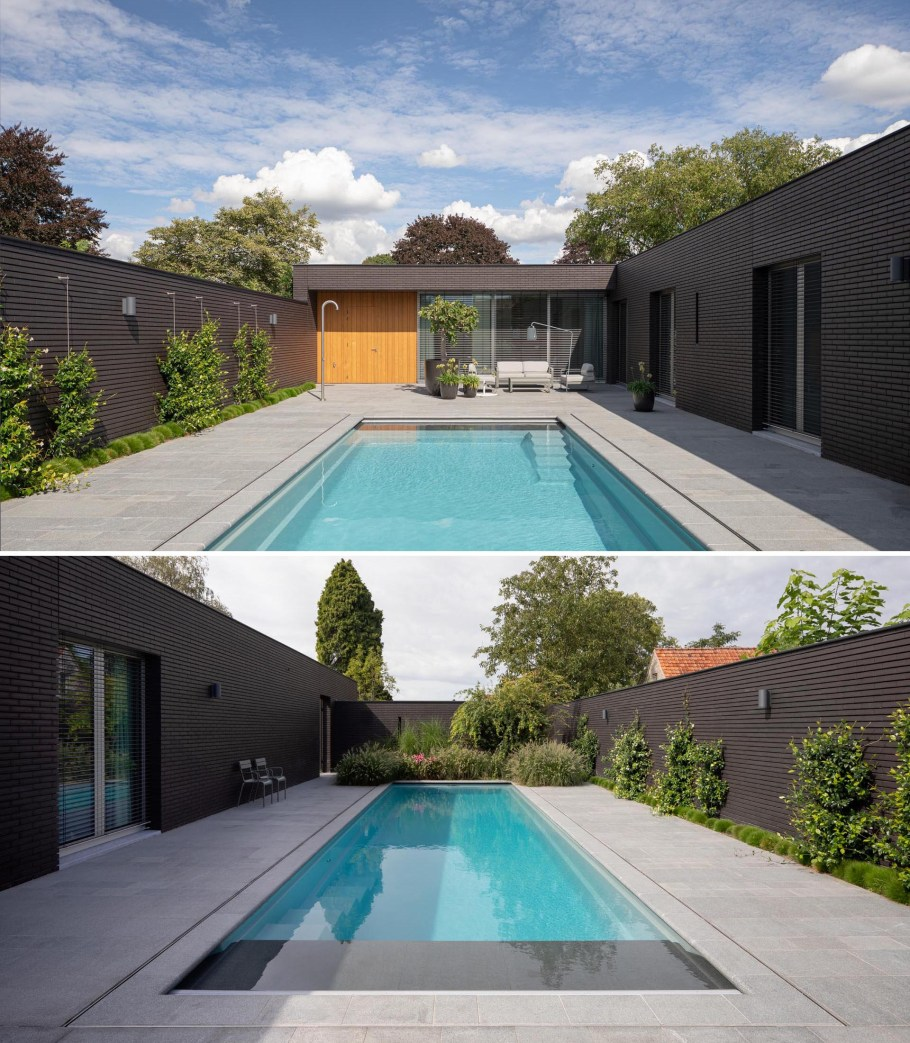 Hidden from the street is a private swimming pool with an outdoor shower and sitting area. Plants have been used as a decorative element along the walls, adding a contrasting element to the black brick.