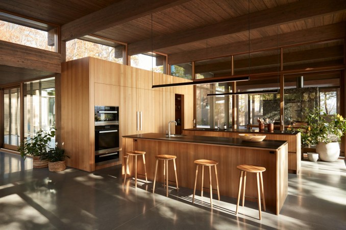 This modern kitchen with two islands also includes flat paneled walnut cabinetry, open shelving, black Fenix NTM countertops, and concrete flooring.