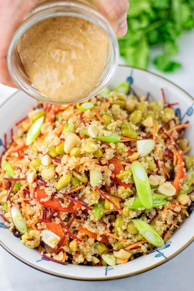 Poring the Thai Peanut Sauce over the quinoa salad.