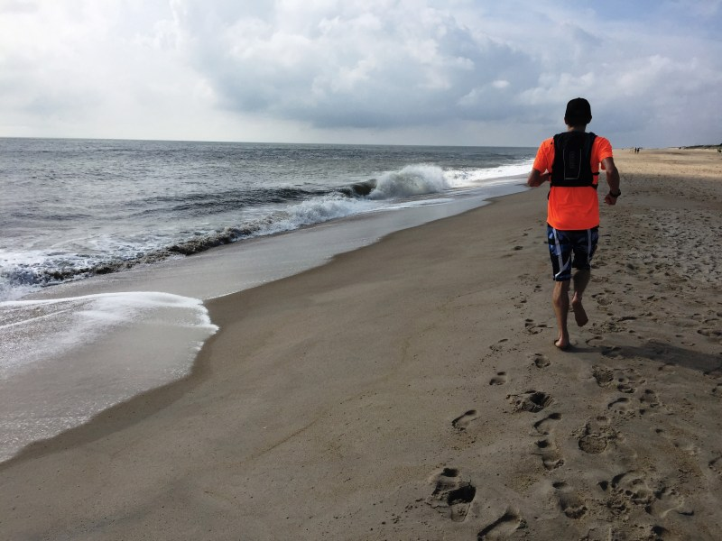 Long Distance Medaling Ultramarathoner Beach Running