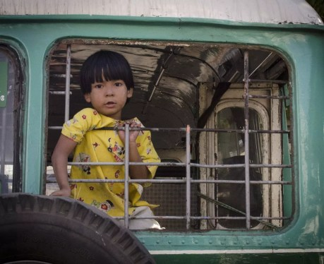 Burma Travel: A kid plays in an old bus