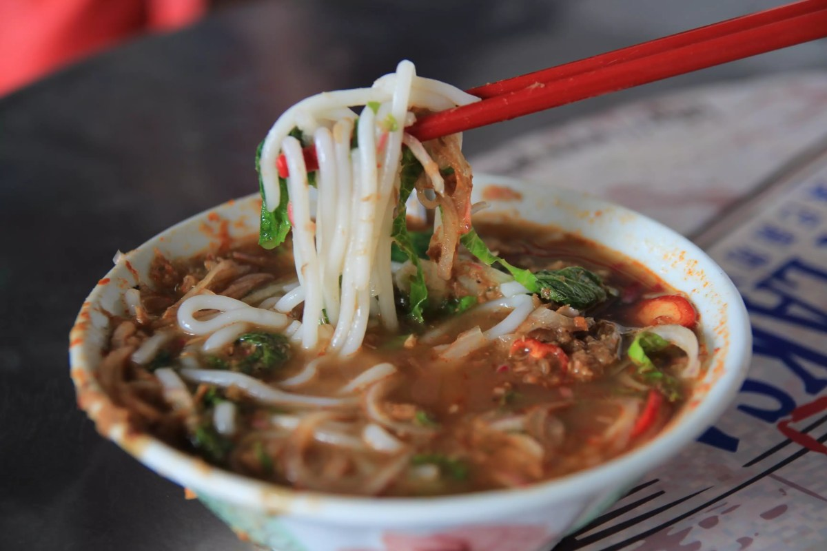 A bowl of spicy rice noodle soup made of broth of different spices