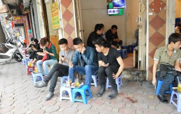 Final de tarde típico em Hanói: jovens tomando chá na calçada, comendo sementes e usando celular.
