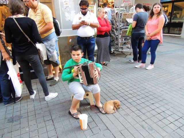 Nessa situação, nós flagramos a mãe do garoto (aquela senhora de rosa parada atrás dele) chegando com ele, o banquinho e o cachorro. Ajeitou o cenário, o menino começou a tocar e ela fingindo que não conhecia, nem olhava para o menino. Só assim, meio de longe...