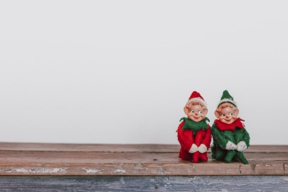 two elf figurines sitting in front of white wall, looking crazed