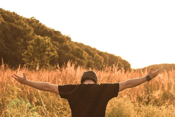 man standing in the middle of field, with his arms wide open.