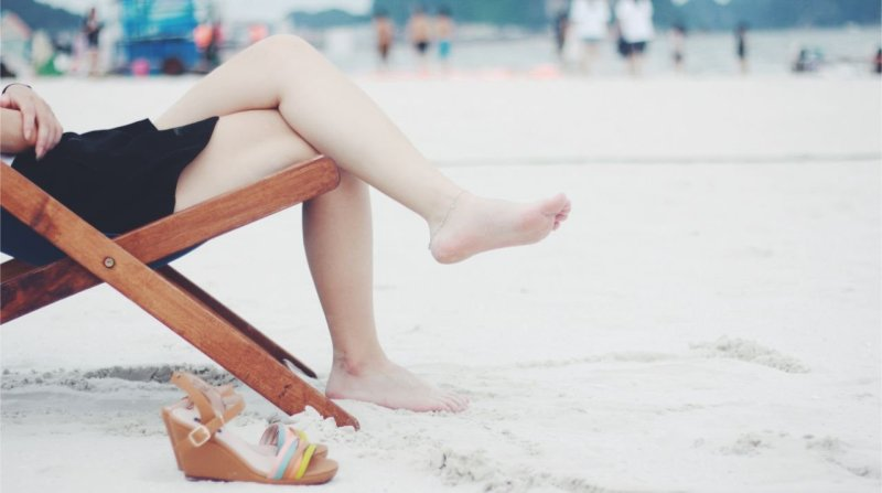 Person sitting on a chair while on the beach