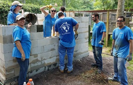 Convergint day Jacksonville Colleagues working on a brick wall