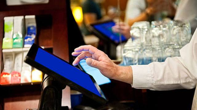 Male server closing a tab out at bar