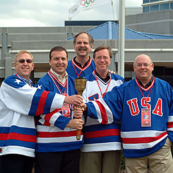Colleagues on stage in U.S.A jerseys holding the torch
