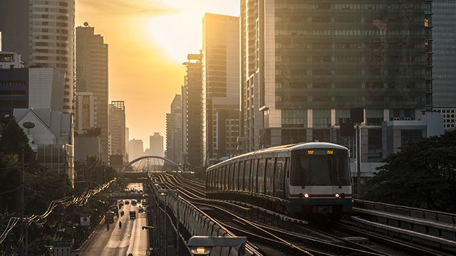 Train moving through sunset across skyline header image