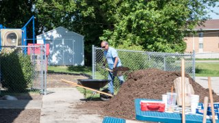 Convergint day male colleague picking up mulch