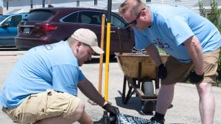 Convergint day male colleagues patching a pothole