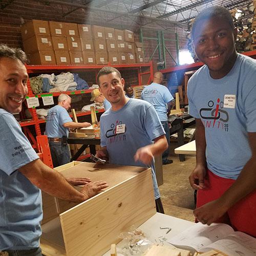 Convergint day Atlanta colleagues building a shelf