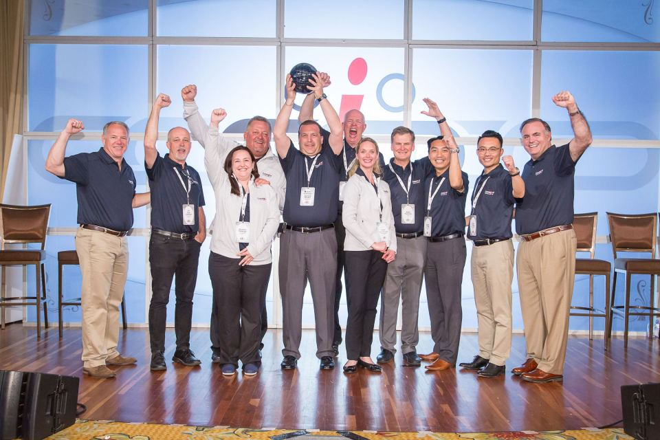 Convergint Colleagues lifting the glob up in group shot