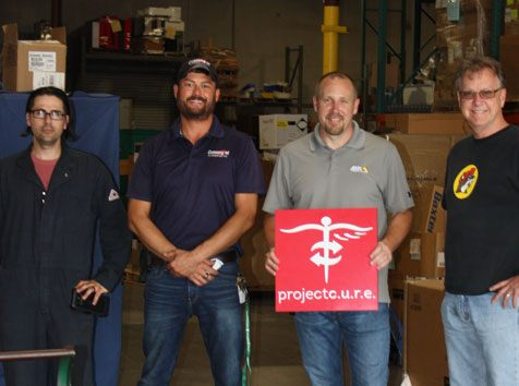 Convergint team with Project C.U.R.E. sign